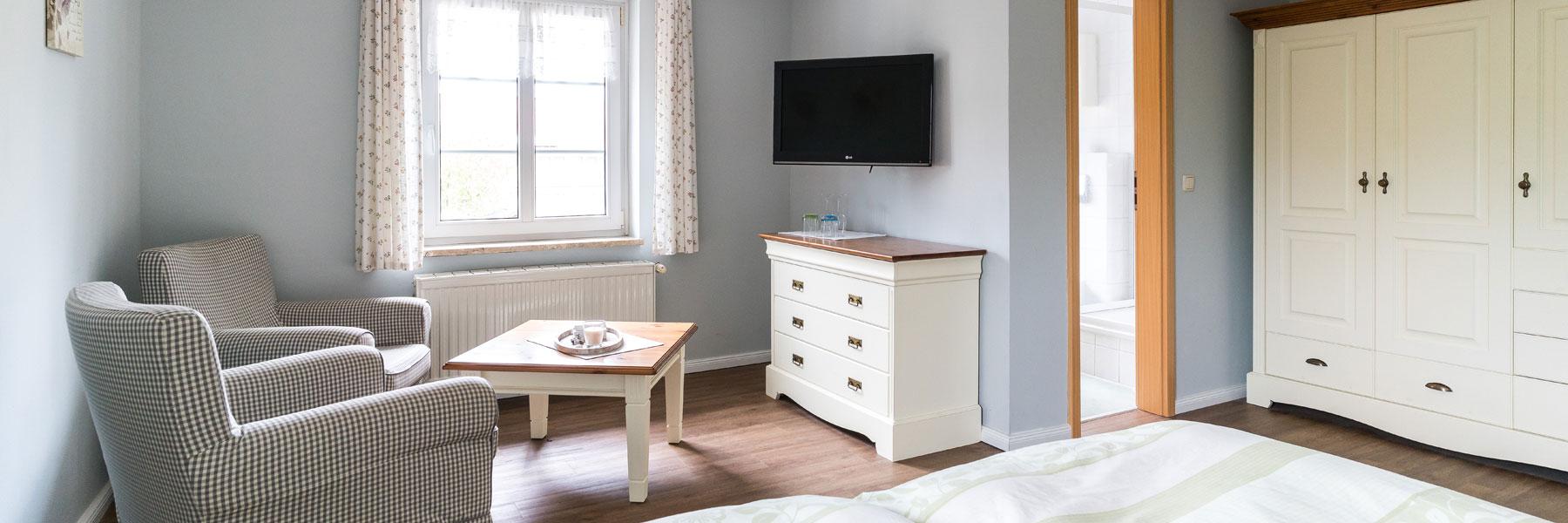 Wohnraum mit Doppelbett und Sitzecke - Gästehaus Bade
