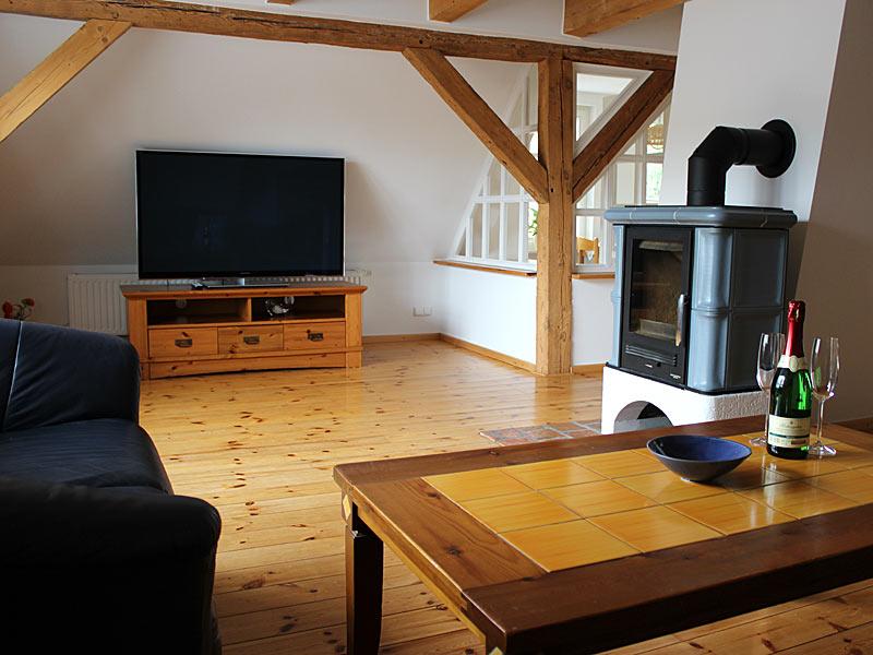 Appartement IV - Wohnraum mit Couchecke, Kamin und TV